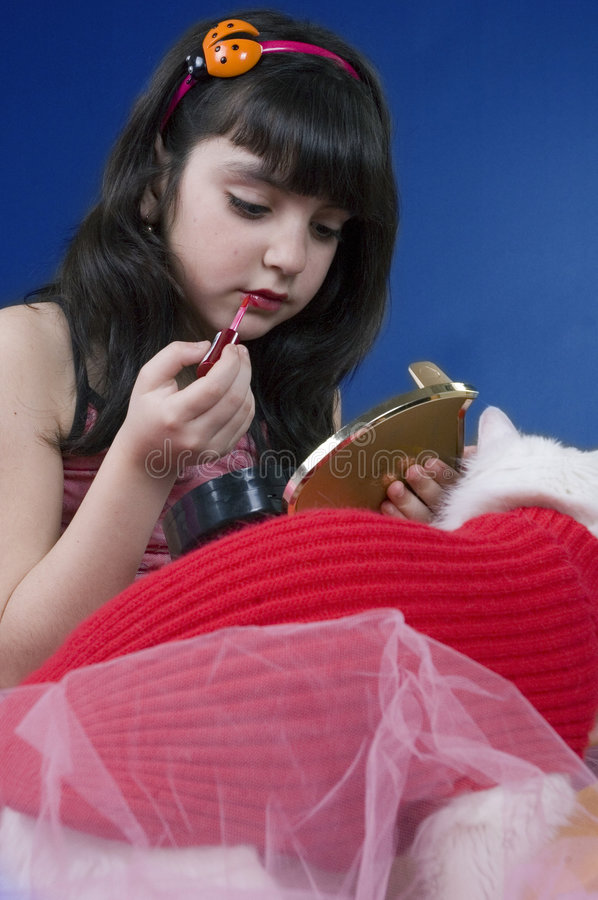 Young girl playing with her make up kit. Surrounded by coloured ballons and a white cat royalty free stock photography