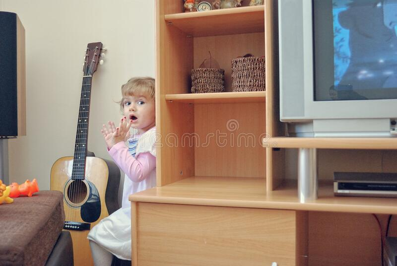 Young Girl Playing Hide-And-Seek At Home. A young girl playing hide-and-seek at home stock photography