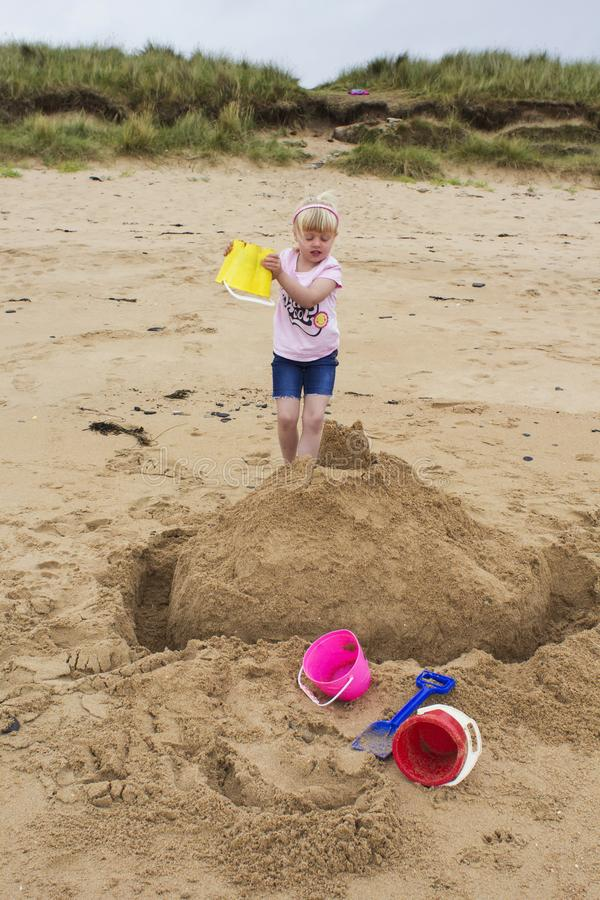 Young girl builds a sand castle stock image