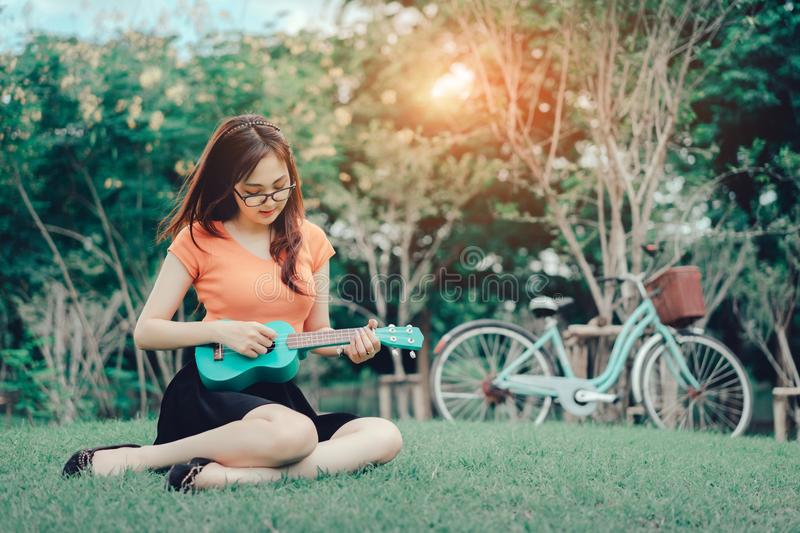 Young girl playing music ukulele outdoor royalty free stock images
