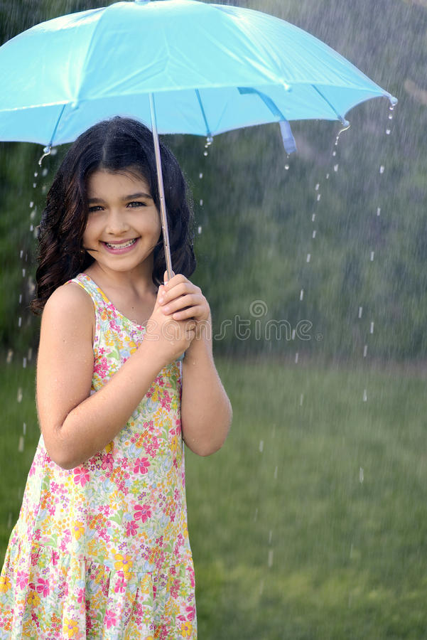 Young girl playing in rain with umbrella stock photo