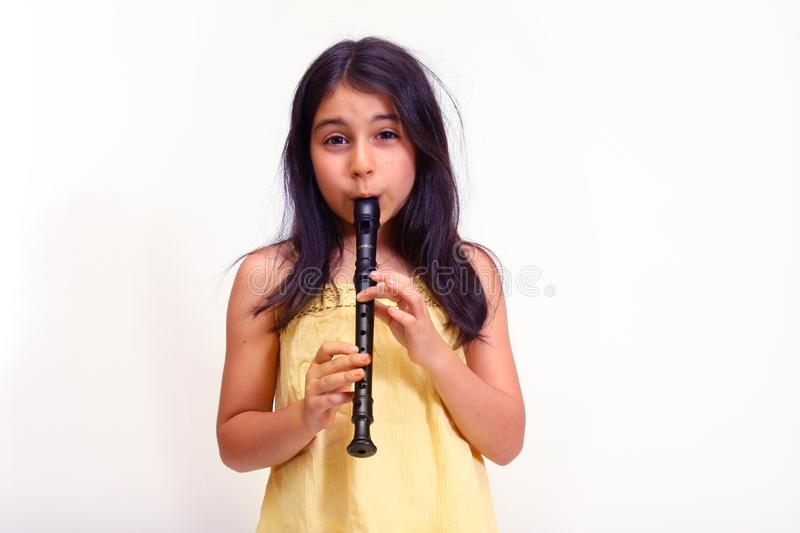 Young girl playing recorder stock image