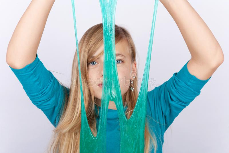 Young girl playing with slime holding it in front of her face royalty free stock photo