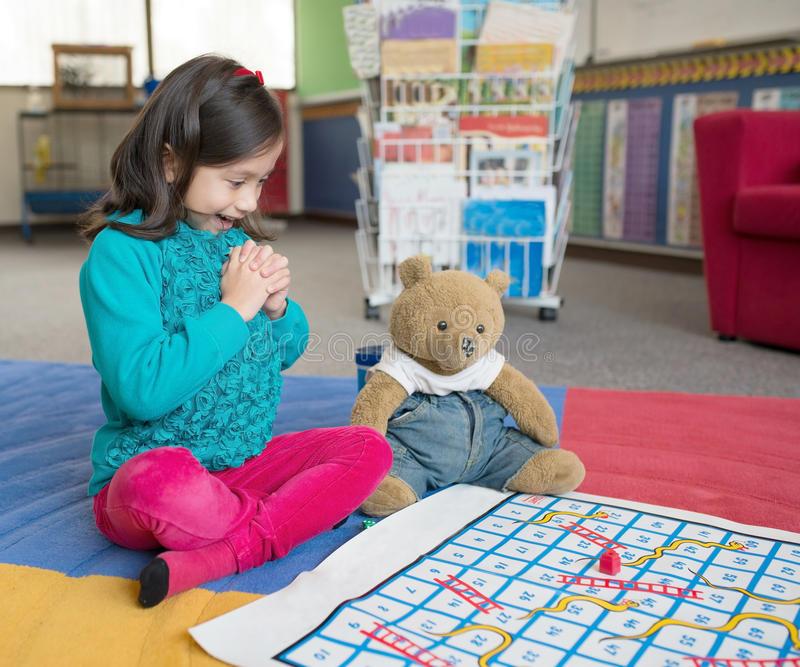 Young Girl Playing Snakes and Ladders. royalty free stock photo