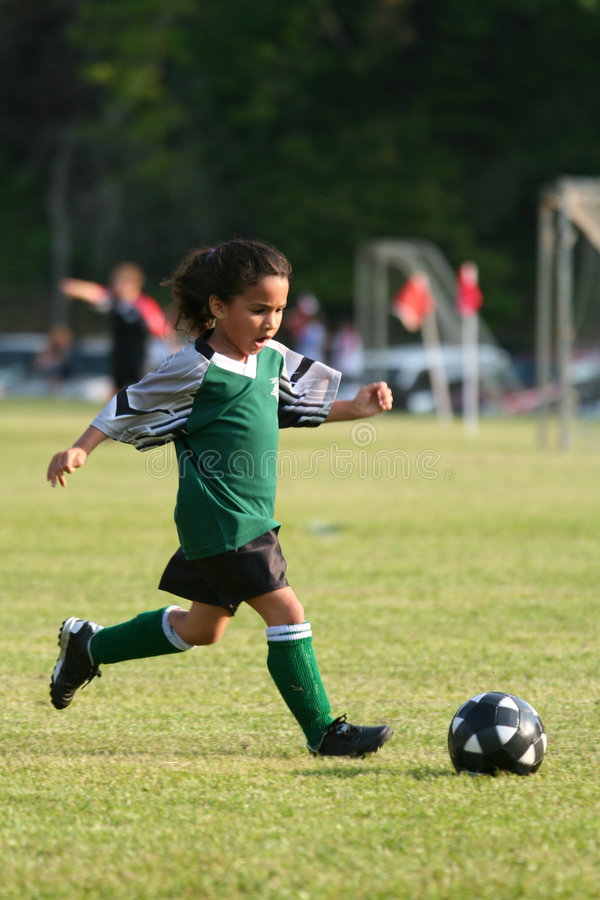 Young Girl Playing Soccer. A young girl playing in a soccer league stock photo