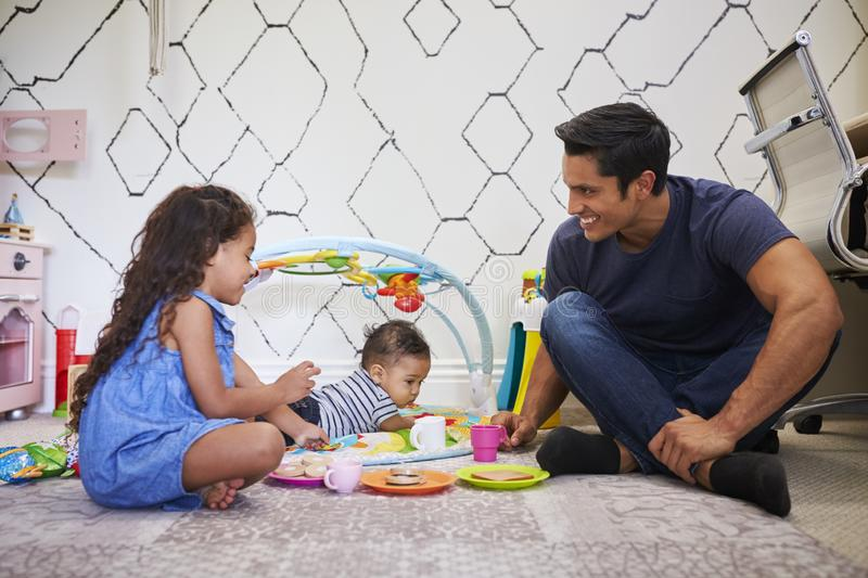Young girl playing tea party with dad, sitting on the floor, baby brother on a play mat beside them stock photography