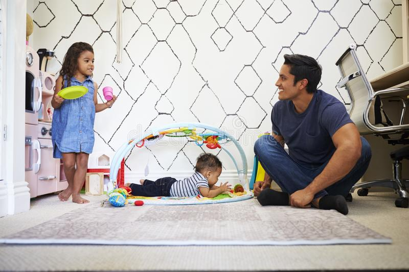 Young girl playing tea party with dad, sitting on the floor, baby brother on a play mat beside them stock photos