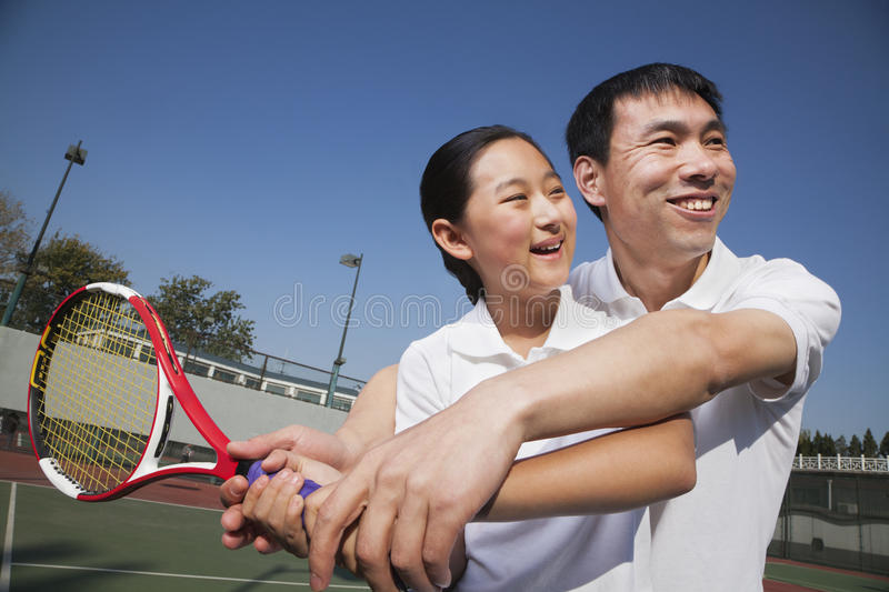 Young girl playing tennis with her coach stock photography