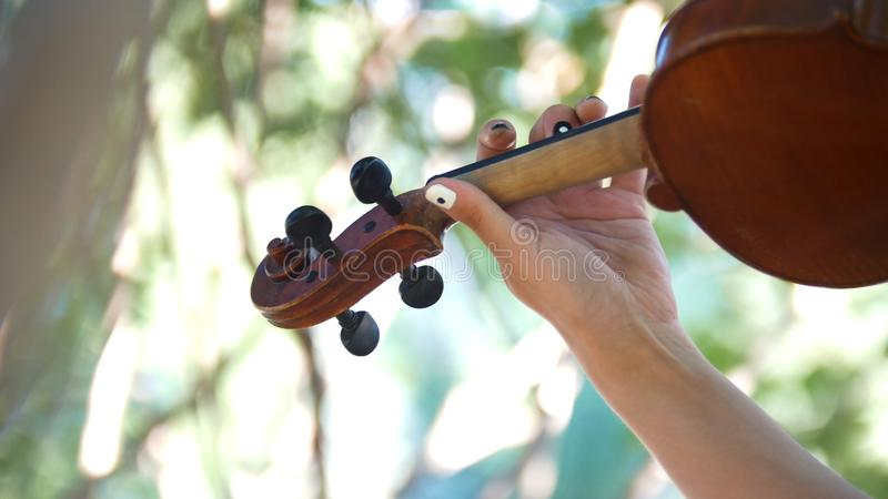 Young girl playing the vintage violin on the nature. Hands stock images