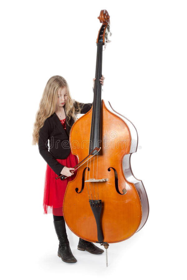 Young girl plays double bass in studio royalty free stock photos