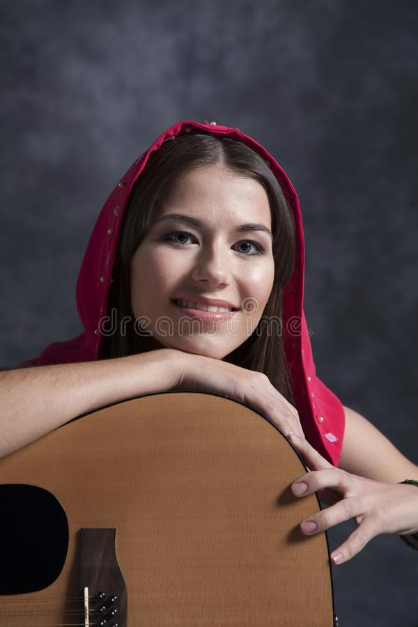 A young girl plays the guitar stock images