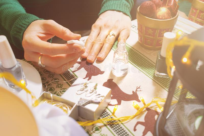 Young girl polishing nails while preparing herself for new years celebration. Decoration on the table royalty free stock photos