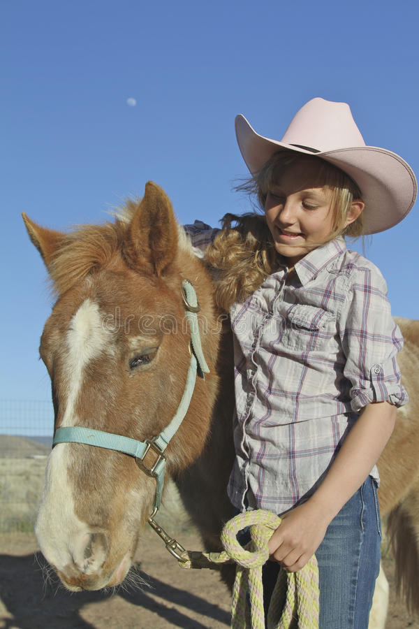 Young Girl and Pony. A young blonde girl show affection for her pony stock photos
