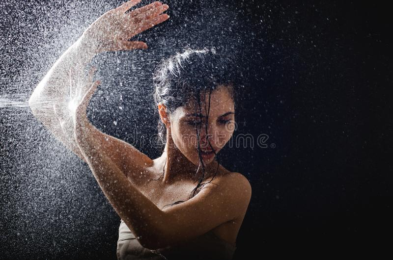 Young girl portrait and splashing water in her face. beautiful female model on black background. Young girl portrait and splashing water in her face. beautiful stock image