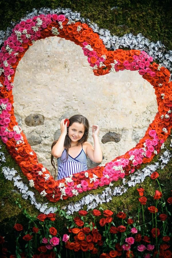 Young girl pose in floral heart, spring. Child smile in flower frame on natural background. Happy valentines day concept. Love symbol, romance. Flower stock photography