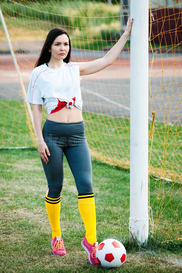 Young girl posing with soccer ball at football goal stock photography
