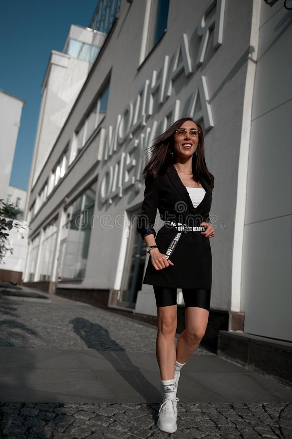Fashionable young model in design clothes. Wall king on the street stock photos