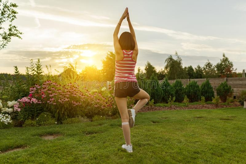Young girl practicing yoga, meditating on a summer sunset background, on green grass, lawn near the house. Young girl practicing yoga, meditating on a summer royalty free stock photo