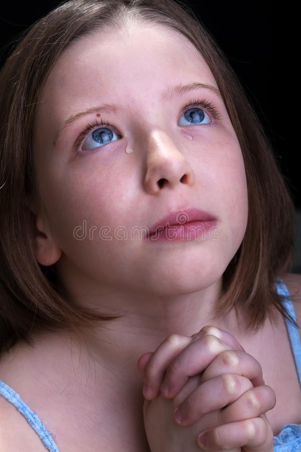 Young girl praying and crying stock photography
