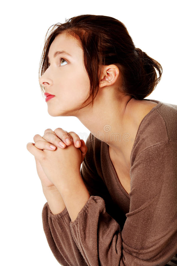 Young girl praying and looking up. Young caucasian girl praying and looking up. Over white background royalty free stock images