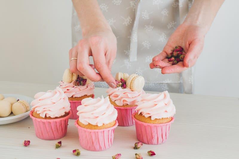 Girl prepares cupcakes stock images