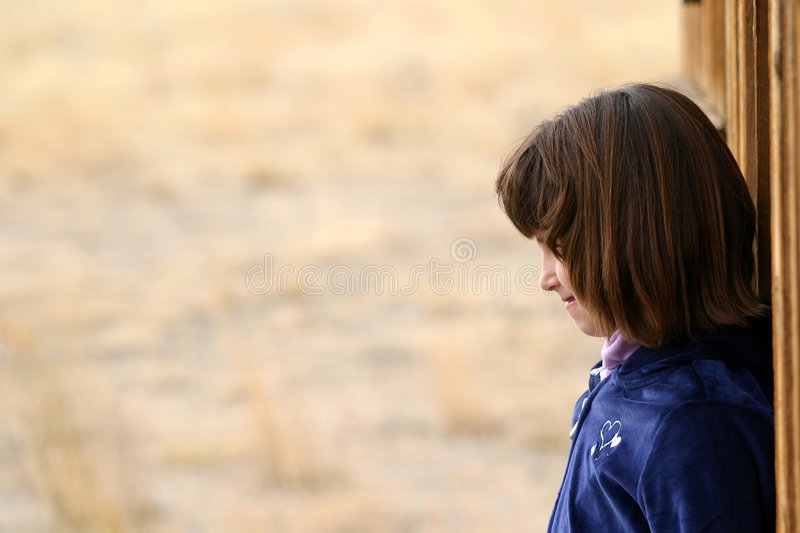 Young Girl Profile. An adorable young Hispanic American girl in the 5 to 8 year old range. Profile view. She is wearing a blue sweater with hearts, smiling and royalty free stock images