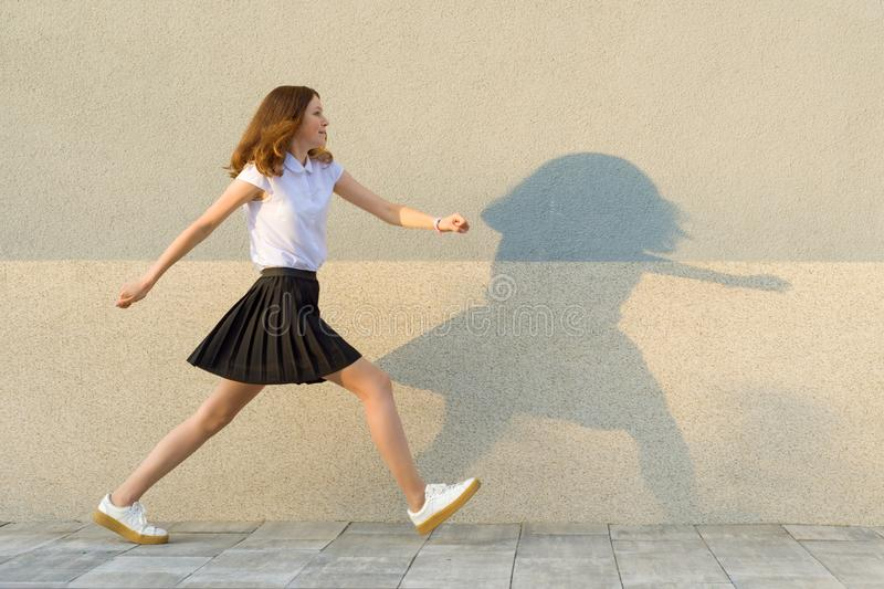 Young girl in the profile, walks along the gray wall, hurry, is late, takes big steps. Outdoor, copy space. royalty free stock photo