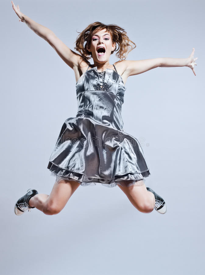 Young girl prom dress jumping screaming happy stock photography