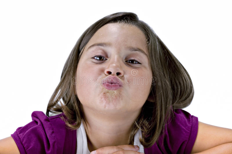 Young Girl with puckered lips. Smiling young brown eyed brunette girl in purple with pursed kissing lips isolated on white royalty free stock photography