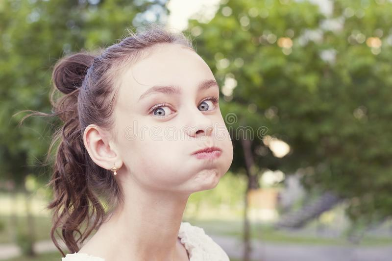 Young girl puffing out her cheeks. Charming girl puffing out her cheeks against park background. Funny beautiful young girl making mouths while having fun stock photo