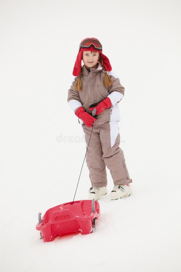 Young Girl Pulling Sledge On Ski Holiday Stock Photo