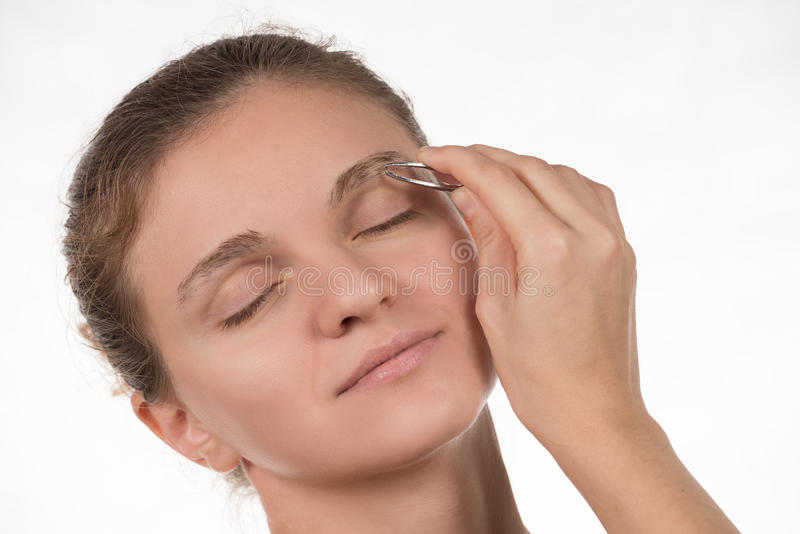 Young girl pulls out her eyebrows with tweezers metal on a white stock photography