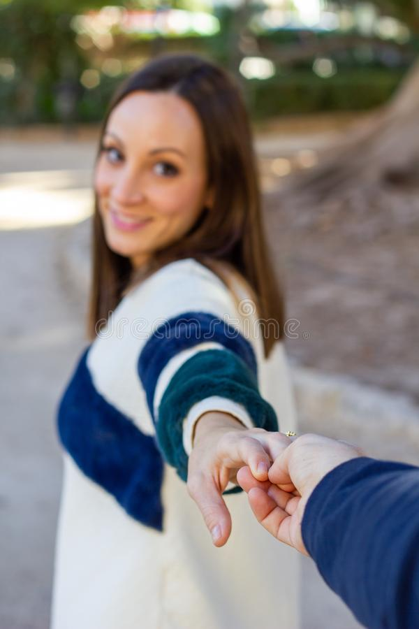 Young girl pulls someone`s hand while walking through an urban park stock images