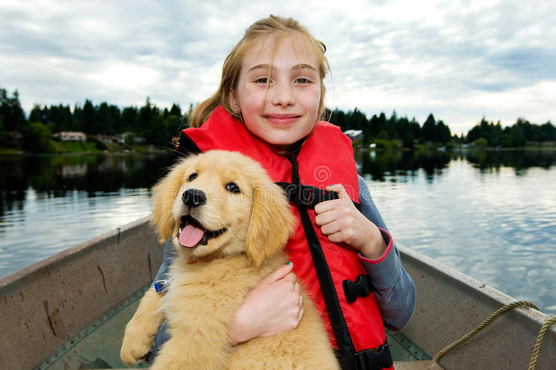 Young Girl with a Puppy on a boat. A cute young kid on a row boat holding a golden retriever puppy while floating on a lake stock photo