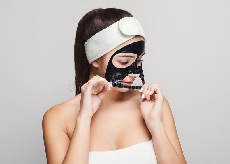 Young girl with purifying black face mask. Skin care. Portrait of young girl peeling off black mask from her face. Purifying spa treatment, white studio royalty free stock photo