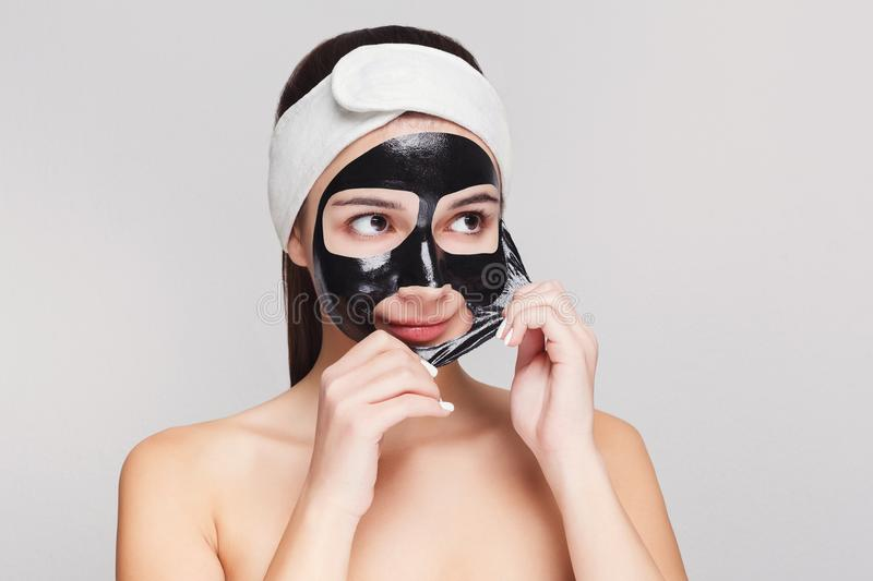 Young girl with purifying black face mask. Skin care. Portrait of young girl peeling off black mask from her face. Purifying spa treatment, white studio stock images