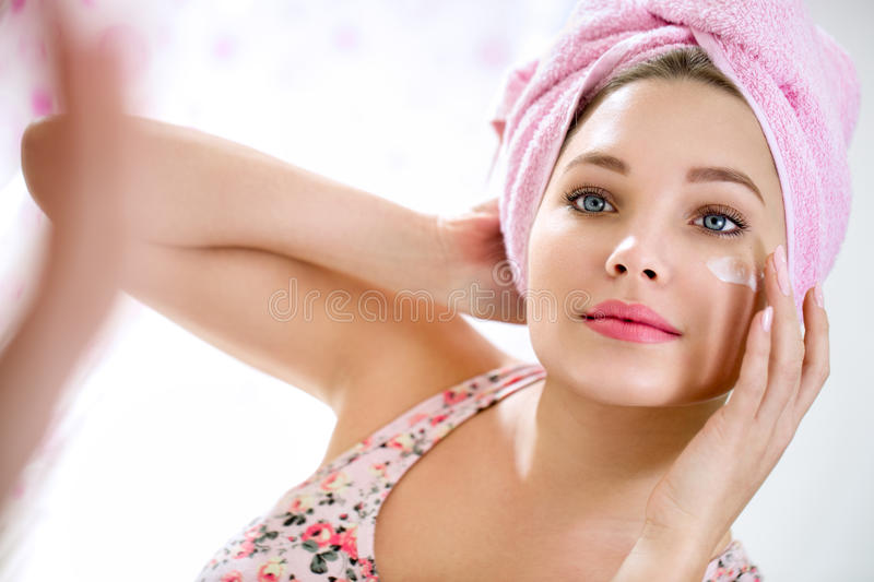 Young girl putting cream on her face. Young girl front of mirror in bathroom putting cream on her face royalty free stock photos