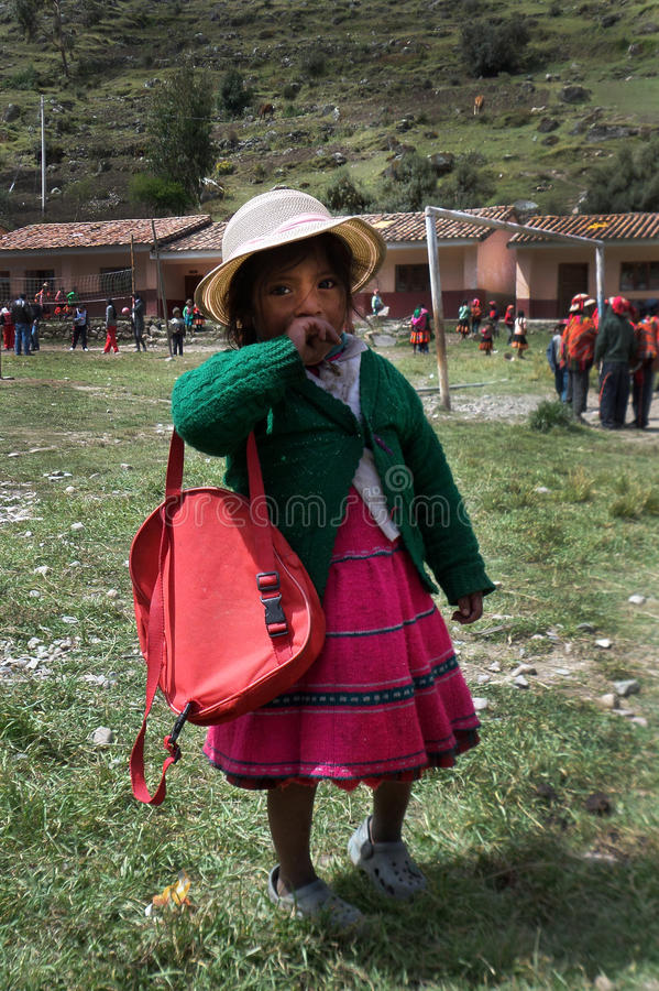 Young Girl in Quechua Village. A young Quechua girl in the schoolyard of a mountain village in Peru. Her classmates play soccer in the background as she shyly stock image
