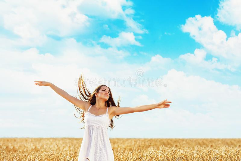 The young girl raised her hands in the rays of sunlight against the background of a field with ripe wheat stock image