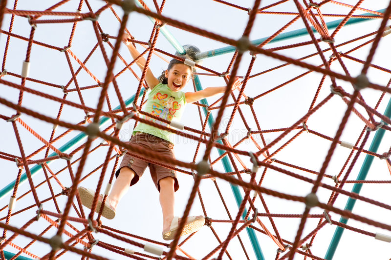 Young girl reached the top of the giant climbing stock photo