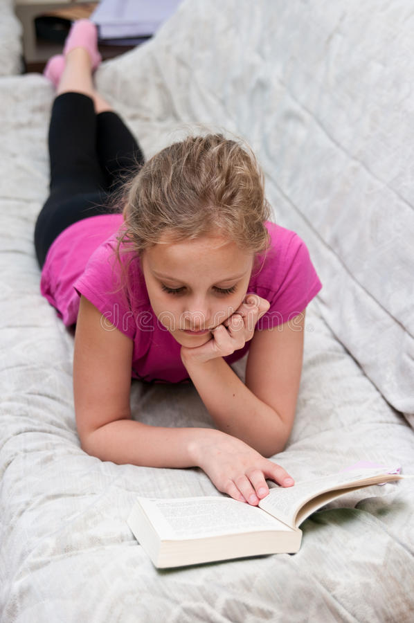 Young girl reading book stock photos