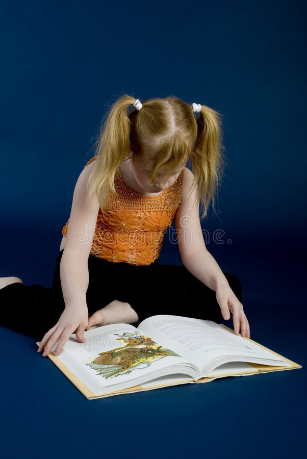 Young girl is reading a book. Young girl is sitting and reading a book royalty free stock photo