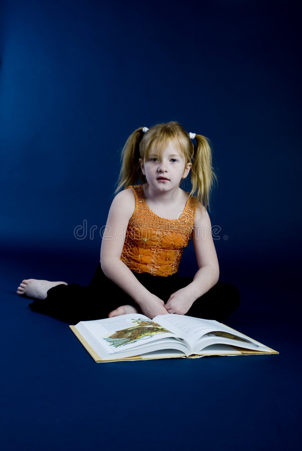 Young girl is reading a book. Young girl is sitting and reading a book royalty free stock photography