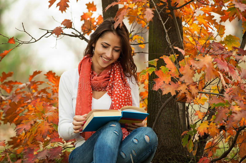 Young girl reading book in autumn park stock photography