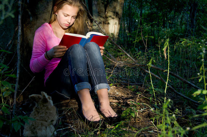 Young girl reading book in forest royalty free stock photography