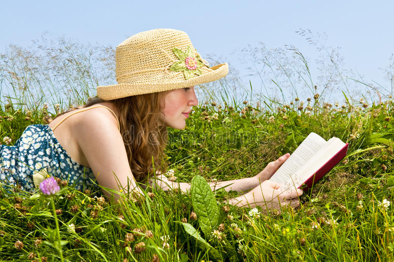 Young girl reading book in meadow stock photo