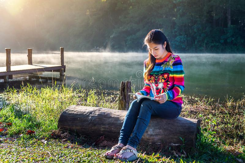 Young girl reading a book in the park stock photo