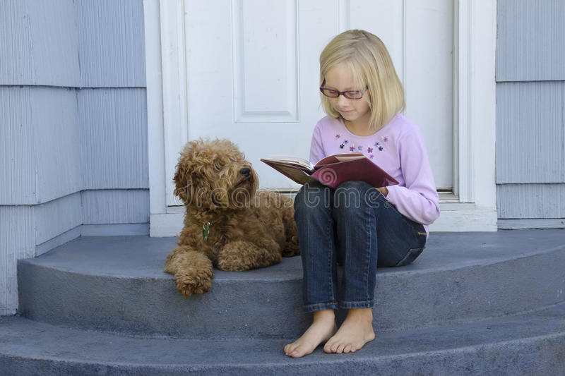 Download Young Girl Reading With Dog At Side Stock Image - Image: 22512601