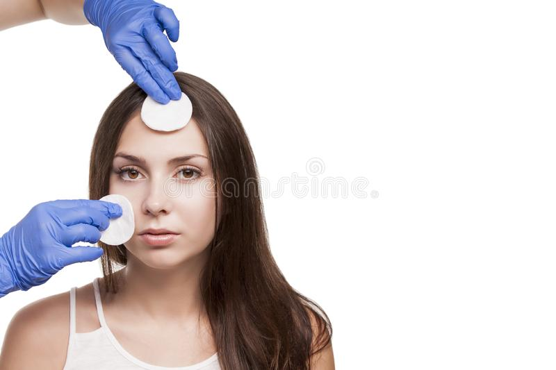 A young girl at the reception at the dermatologist. Cleaning with cotton pads. The doctor in blue gloves. Perfect skin. stock images