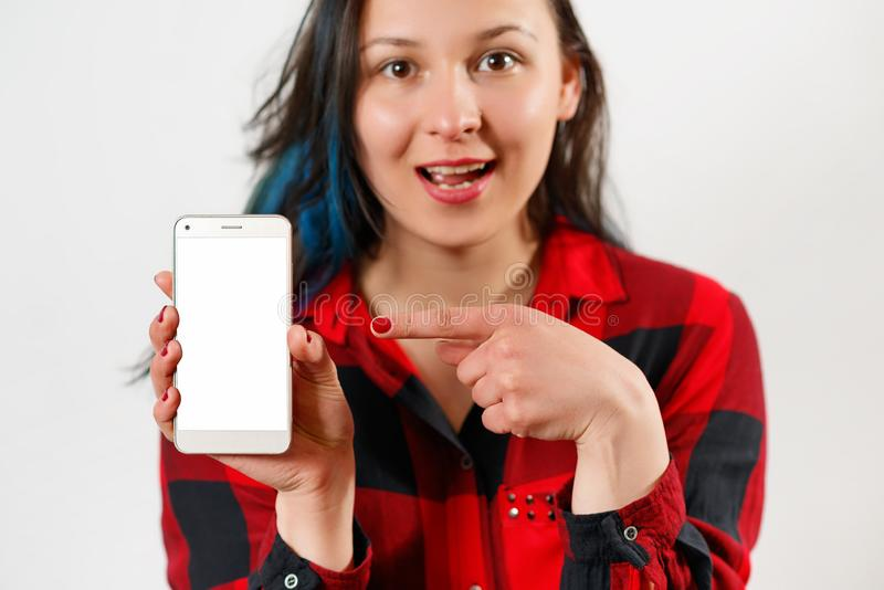A young girl in a red and black shirt holds a smartphone with an empty white screen vertically in front of her, points at it with. Her finger and smiles at the stock photos